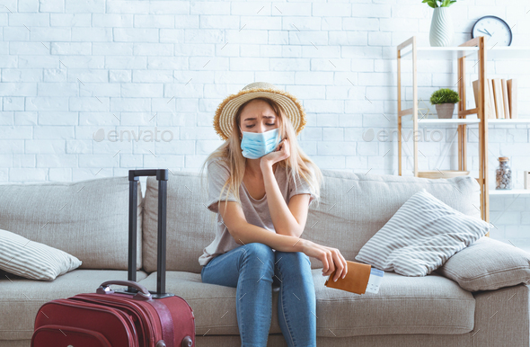 Quarantine concept. Sad girl with suitcase holding passport - Stock Photo - Images