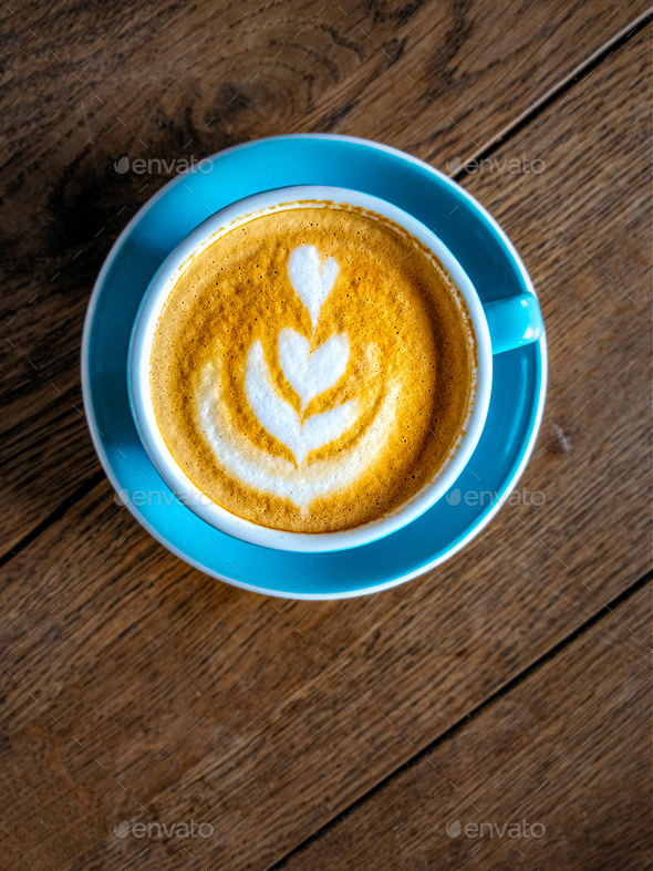 Close-up detail of coffee in a colorful cup on wooden table, vintage style - Stock Photo - Images