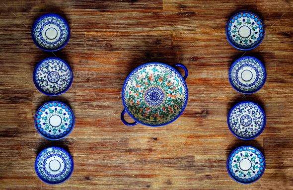 Detail of painted ornate pottery plates on wooden textured table in vintage style - Stock Photo - Images
