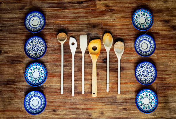 Detail of wooden cooking spoons and painted ornate plates on textured wooden table, vintage style - Stock Photo - Images