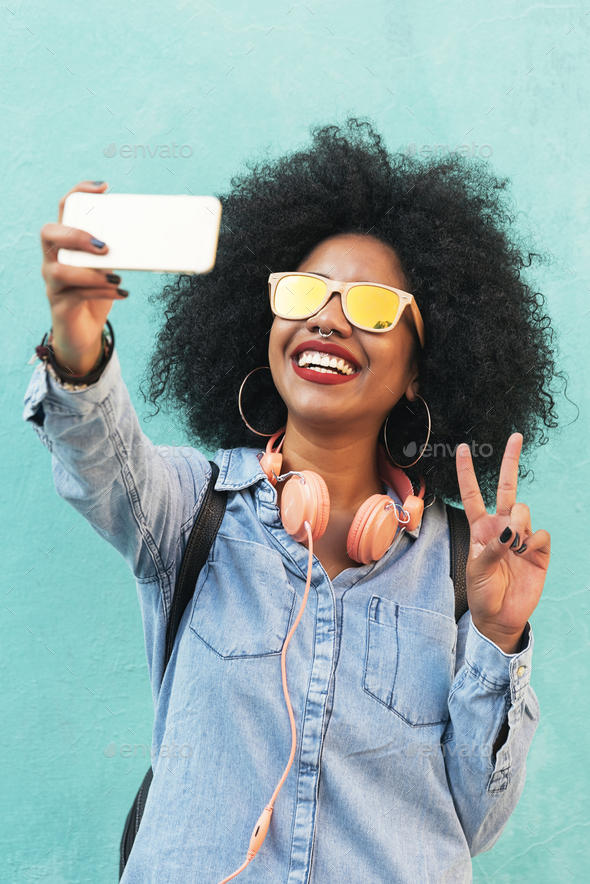 Self portrait of beautiful young afro american woman making peace sign. - Stock Photo - Images