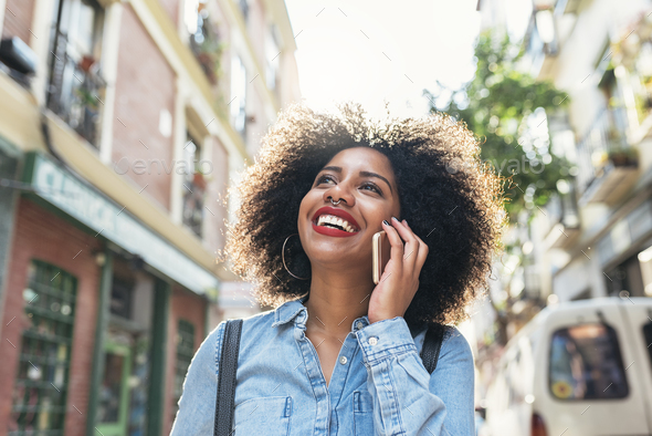 Beautiful afro american woman using her mobile in the street. - Stock Photo - Images
