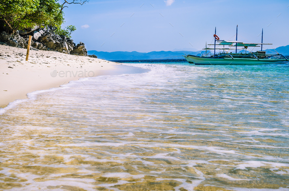 Traditional banca boat in clear water at sandy Beach near El Nido, Philippines - Stock Photo - Images