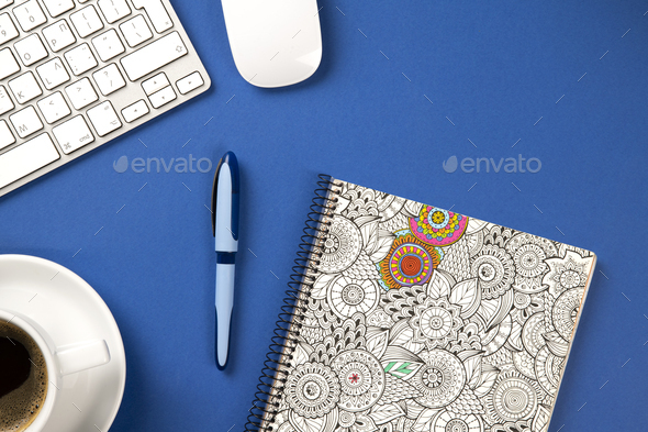 Blue office desk with notebook, pen, keyboard, mouse and a coffee - Stock Photo - Images