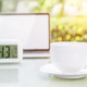 Coffee cup and laptop at office with digital clock - PhotoDune Item for Sale