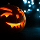 carved face of pumpkin glowing on Halloween on blue bokeh light background - PhotoDune Item for Sale