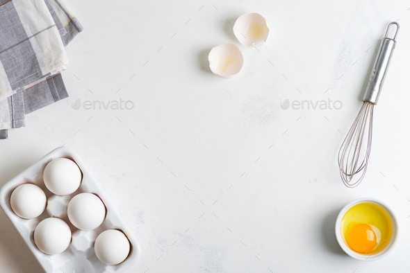 Ceramic box with natural organic farm eggs and metal whisk on a stone kitchen table - Stock Photo - Images