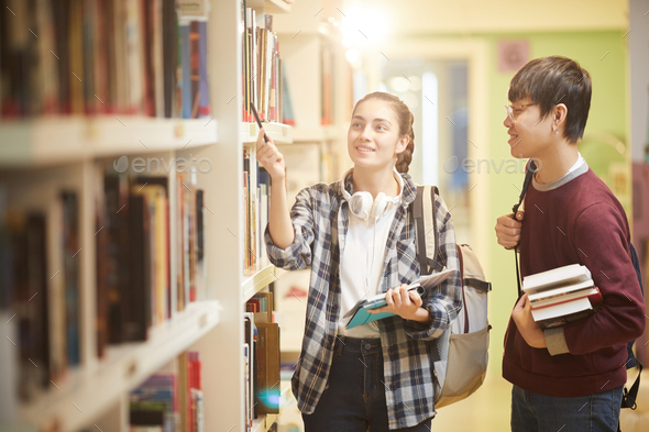 Students taking books in the library - Stock Photo - Images