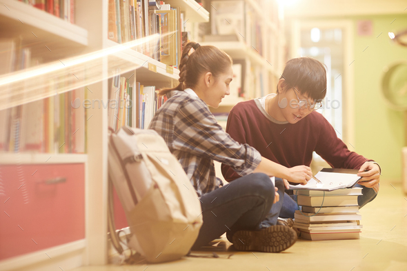 Students studying in the library - Stock Photo - Images