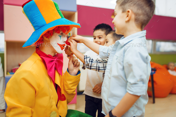 Little joyful boy touches red clown's nose - Stock Photo - Images