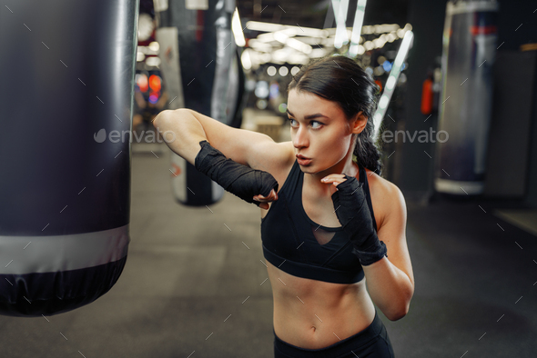 Woman hits a punching bag, thai boxing training - Stock Photo - Images