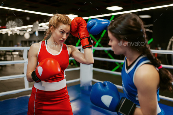 Women in red and blue gloves boxing on the ring - Stock Photo - Images
