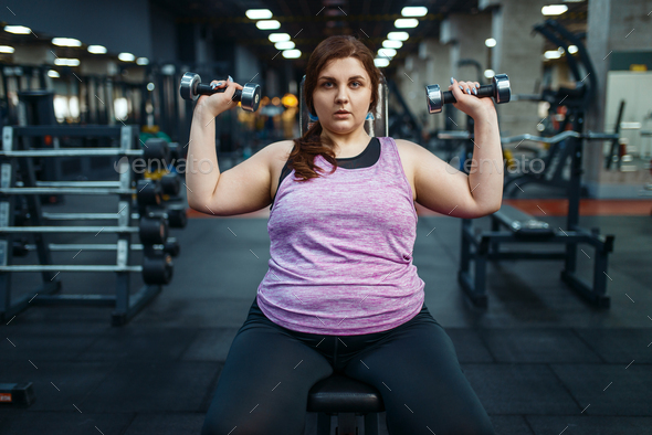 Overweight woman poses with dumbbells in gym - Stock Photo - Images