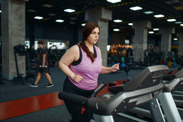 Overweight woman, exercise on treadmill in gym - Stock Photo - Images