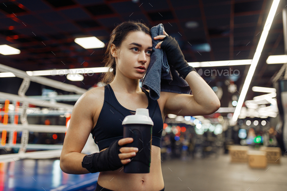 Tired woman wipes her sweat after boxing training - Stock Photo - Images