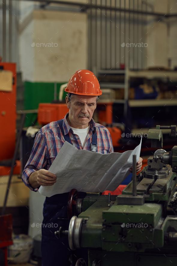 Engineer examining the blueprint - Stock Photo - Images