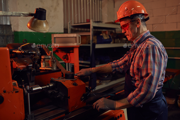 Engineer controlling the lathe - Stock Photo - Images