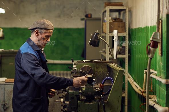 Mature mechanic working at lathe - Stock Photo - Images