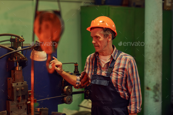 Manual worker working at machine - Stock Photo - Images