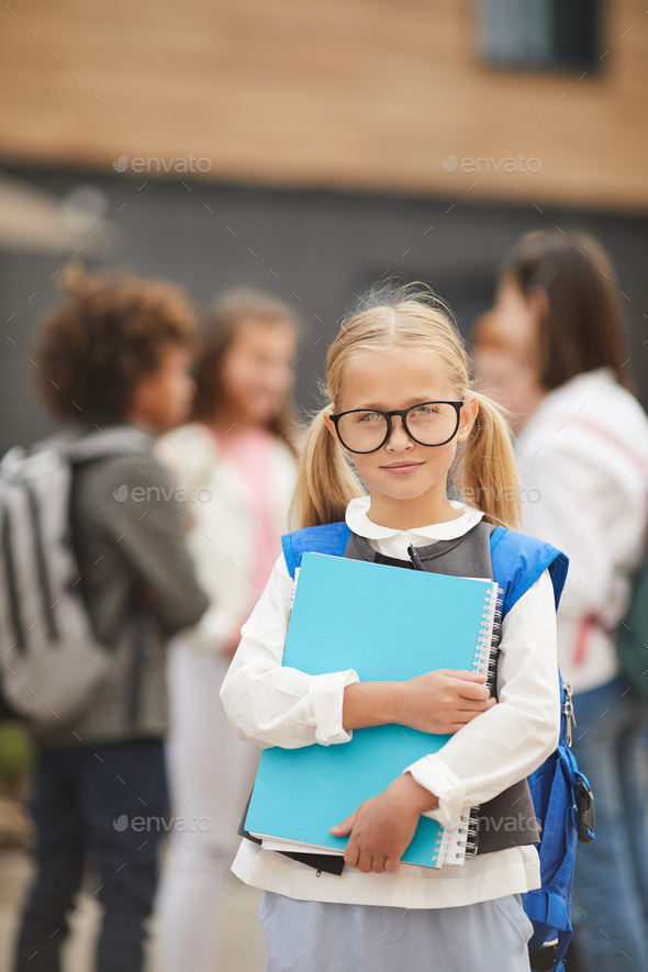 Schoolgirl with textbooks outdoors - Stock Photo - Images