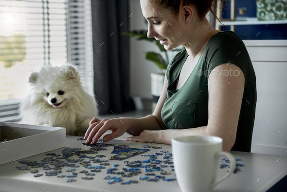 Young woman doing jigsaw puzzles - Stock Photo - Images