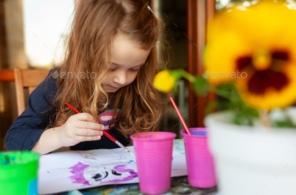 Three year old girl paints with watercolors on the terrace. - Stock Photo - Images