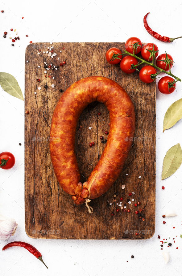 Smoked sausage on white kitchen table background with aromatic herbs and spices - Stock Photo - Images