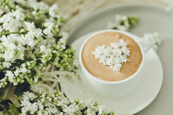 Composition with the branches of lilac and fresh coffee with foam in white cup - Stock Photo - Images