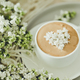 Composition with the branches of lilac and fresh coffee with foam in white cup - PhotoDune Item for Sale