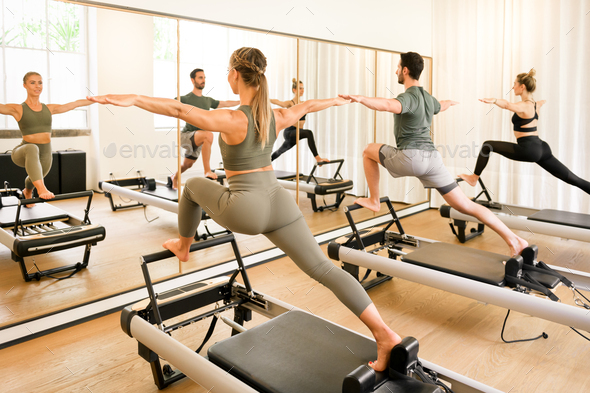 Pilates class of athletes doing a standing lunge exercise - Stock Photo - Images