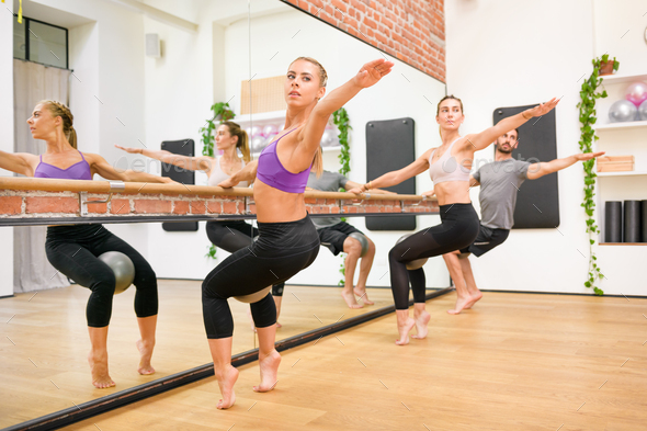 Group of athletes doing spinal twist exercises - Stock Photo - Images