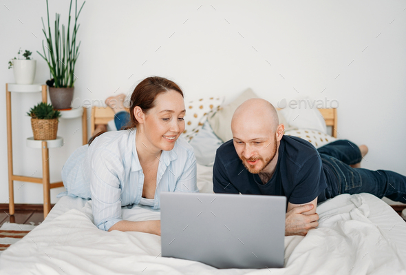 Adult married couple in casual clothing using open laptop lie on bed - Stock Photo - Images