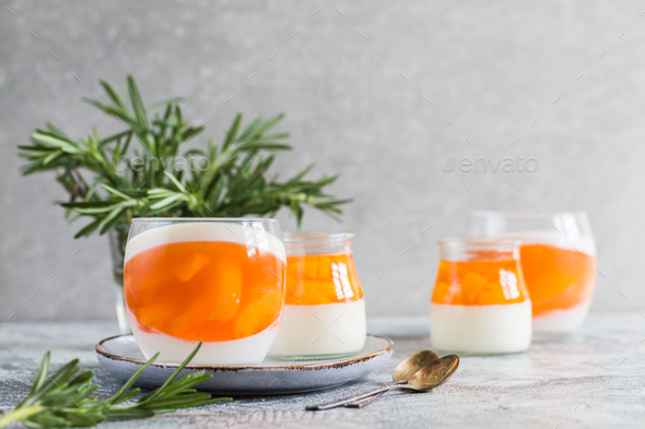 homemade panna cotta with slices of peach and peach jelly in glass jars - Stock Photo - Images