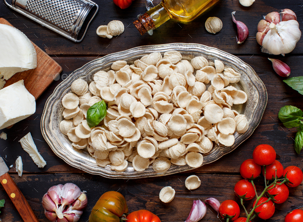 Fresh raw  italian pasta orecchiette, vegetables, herbs and olive oil - Stock Photo - Images