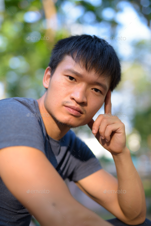 Portrait of young Asian man sitting at the park outdoors - Stock Photo - Images