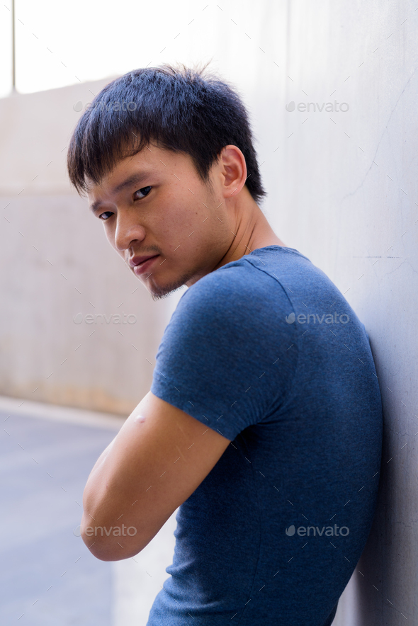 Portrait of young Asian man thinking against the wall outdoors - Stock Photo - Images