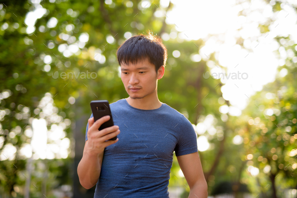 Portrait of young Asian man using phone at the park outdoors - Stock Photo - Images