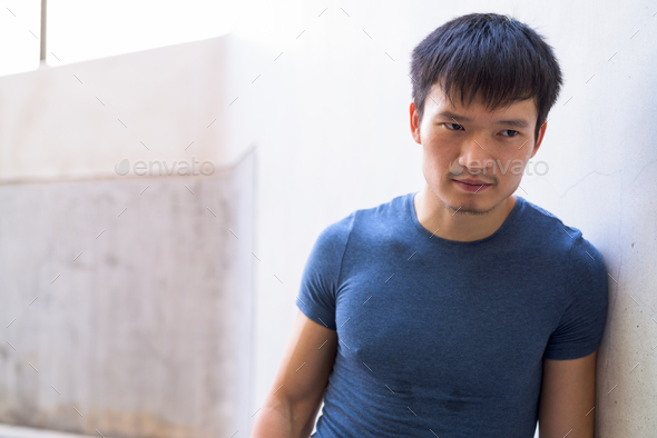 Portrait of young Asian man leaning on wall outdoors - Stock Photo - Images