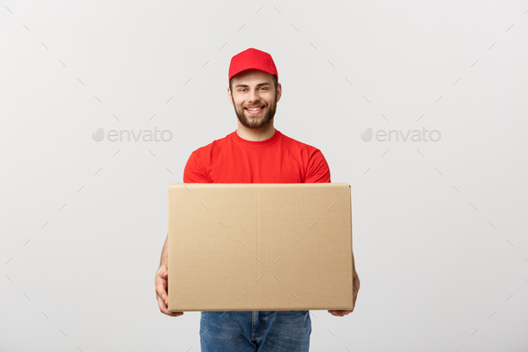 Young smiling logistic delivery man in red uniform holding the box on white background - Stock Photo - Images