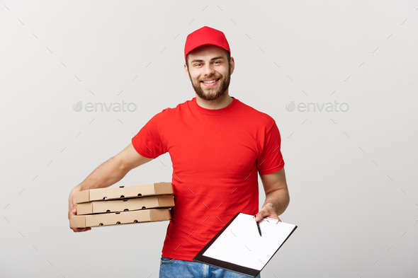 Delivery Concept: Young handsome delivery man with pizza boxes giving you a document to sign - Stock Photo - Images