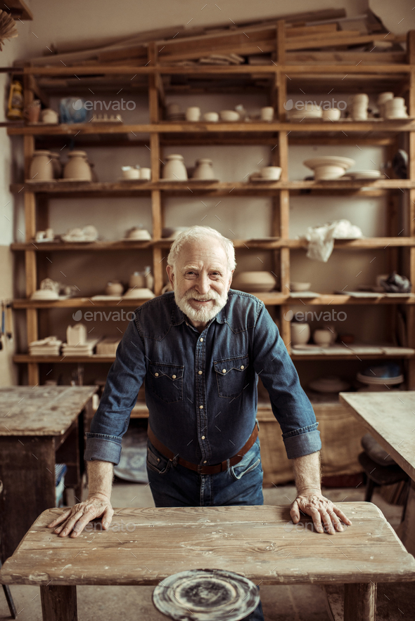 Senior Potter Standing and Leaning on Table - Stock Photo - Images