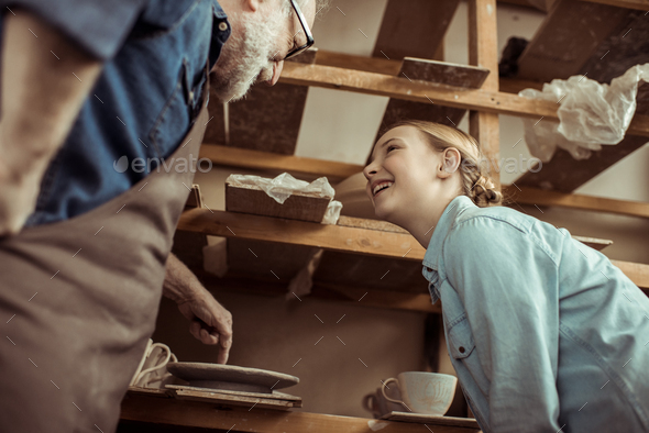 Grandfather Explaining To Granddaughter How To Use Pottery Wheel - Stock Photo - Images