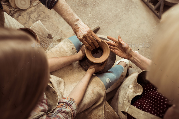 Overhead view of little girl making pottery on wheel with help of grandparents at workshop - Stock Photo - Images