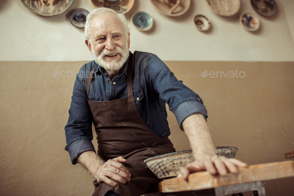 Senior Potter in Apron Sitting on Table Against Wall With Hanging Pottery Goods - Stock Photo - Images