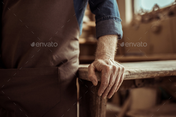 Cropped Image of Potter Standing and Leaning on Table at Workshop - Stock Photo - Images