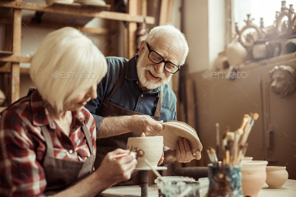 Woman Painting Clay Pot With Senior Potter at Workshop - Stock Photo - Images