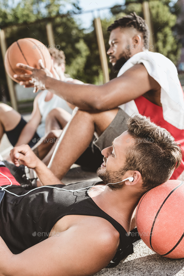 Multiethnic Basketball Team Resting After Game on Basketball Court Together - Stock Photo - Images