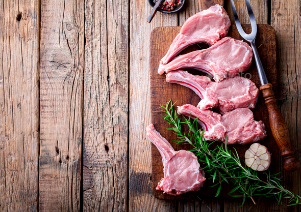 Raw fresh meat Veal rib Steak on bone and meat fork  on a wooden vintage background . Food Concept - Stock Photo - Images