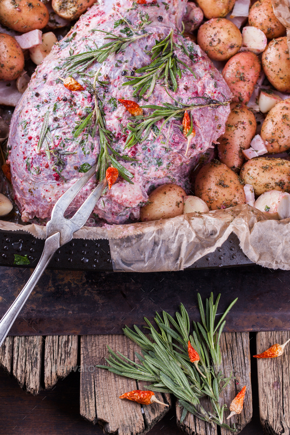 Raw lamb leg marinated with spices, garlic and rosemary, with a young potato - Stock Photo - Images