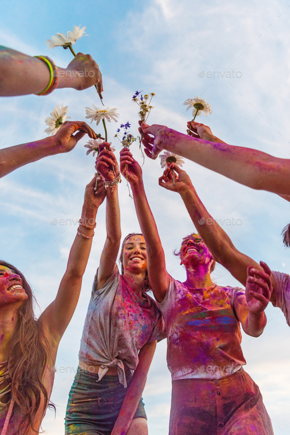 Cheerful Young Friends With Colorful Paint on Clothes Holding Chamomiles at Holi Festival - Stock Photo - Images